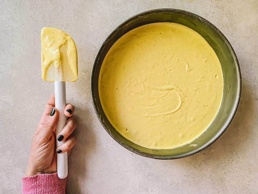 Hand med slev och en fylld cheesecake