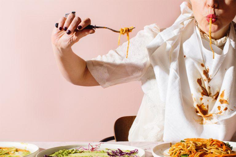 Kvinna äter pasta och någon sås