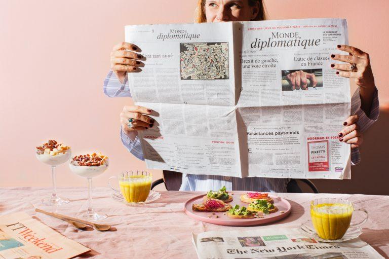 Fyra händer som håller i en tidning vid ett frukostbord