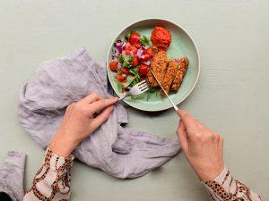 Händer skär en vegansk köttfärslimpa
